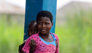 Beninese girl carries her sister in a village over the lake Nokwe