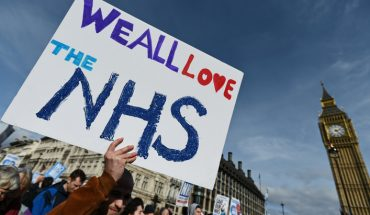 Protesters march past Parliament during a demonstration in support of the NHS