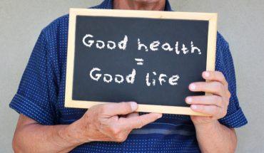 ‹man holding balckboard: good health, good life